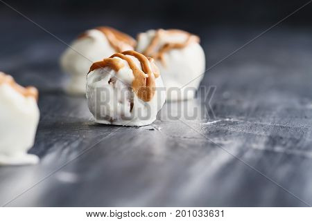 White Chocolate truffles for Christmas or Valentines's Day drizzled with peanut butter sauce. Extreme shallow depth of field with selective focus on center candy.