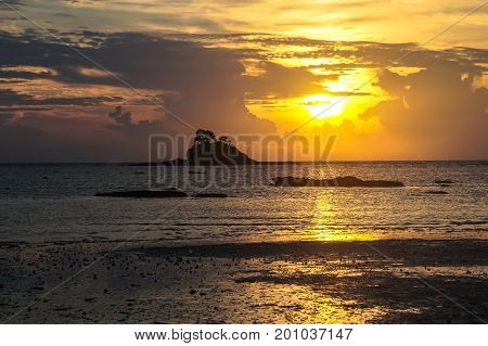 Beautiful sea sunset with island silhouette on the beach at low tide & reflections in the sand.