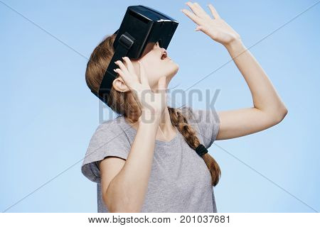 Young woman on a Blue background with virtual reality glasses.