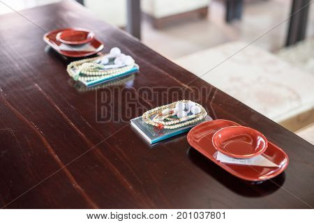 Prayer book and sake cup couple on table for drink sake ceremony in japanese buddhist nichiren or shinto wedding ceremony