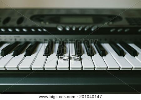Wedding Rings On The Black-and-white Keys Of The Piano. Unusual Jewelry Photo