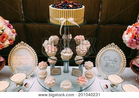 Candy Bar. Delicious Sweet Buffet With Cupcakes And Wedding Cake. Sweet Holiday Buffet With Chocolat