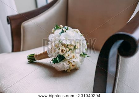 Wedding Bouquet Of White Roses Lies On Luxury Armchair.