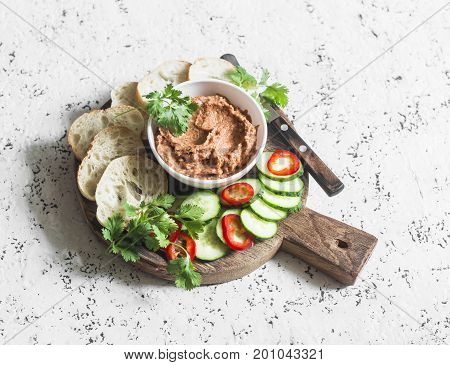 Eggplant smoked paprika walnuts dip vegetables and bread on wooden cutting board on a light background. Vegetarian snack