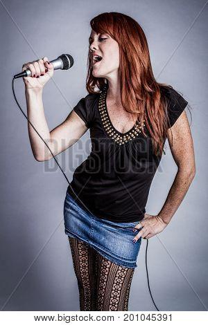 Redhead girl singing karaoke with microphone