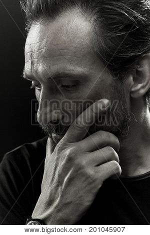 Monochrome portrait of mature male showing emotion of sorrow. Close up view of a man holding hand on his face.