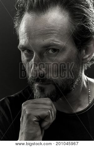 Black and white portrait of a beardy man with serious look on his face. Brutal man on black background.