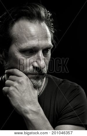 Mid age crisis concept, male looking aside holding hand on face. Black and white portrait of thoughtful mature man.