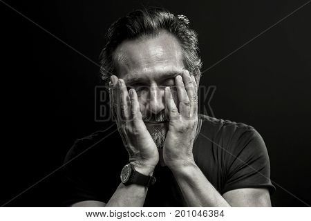 Monochrome portrait of mature man in crisis. Male covering his face with hands showing emotions of sorrow and regret.