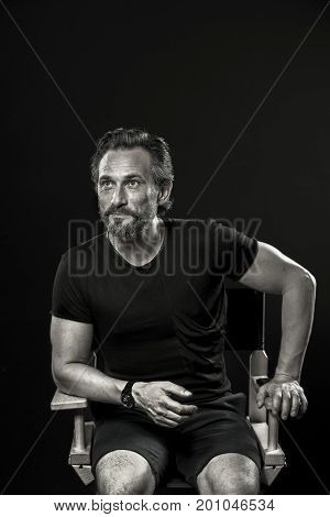 Self confident man with cunning face sitting on chair. Black and white portrait of mature man isolated on black background.