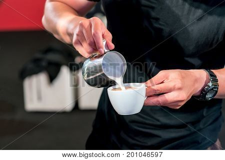 Barista hand pouring fresh milk foam into espresso cup for latte art.