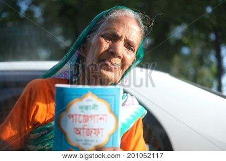 Dhaka, bangladesh, august 2017- a old women selling books at street taken from car located at dhaka city in bangladesh taken on 24 , august 2017