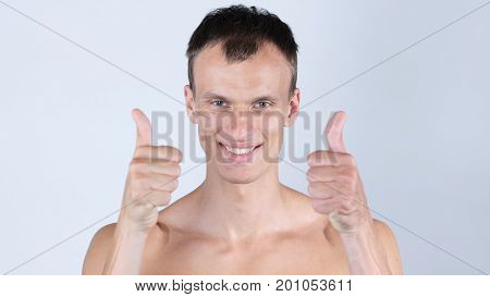 Portrait Of Young Shirtless Man Shows Thumbs Up With Both Hands
