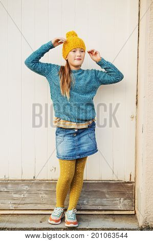 Outdoor fashion portrait of cute 9 year old little girl wearing yellow hat blue pullover denim skirt and polka dot tights