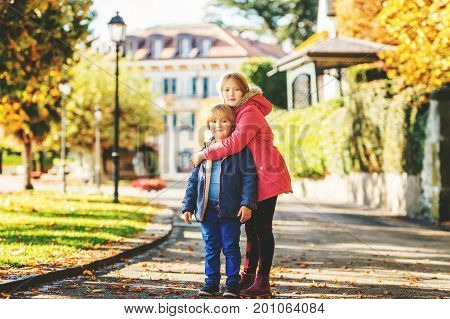 Big sister and small brother playing in autumn park kids wearing bright warm jackets