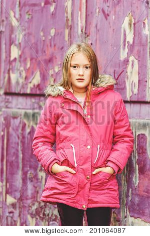 Outdoor vertical portrait of cute 9 year old little girl wearing pink winter coat standing next to purple background