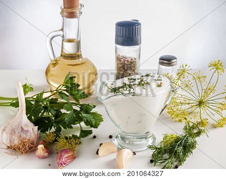 Cooked sour cream sauce with garlic herbs parsley dill herbs pepper in a glass bowl on a white background with butter in a bottle with pepper and salt jars