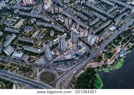 Residential district in a large metropolis with road junctions and houses. View of a newly built residential complex with a shopping center on the lower floors. Aerial view. From above