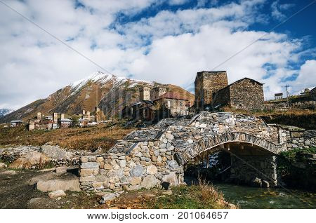Ancient stone bridge over Enguri river and traditional Svan Towers and machub houses with flagstone in Ushguli commune Upper Svaneti Georgia. Georgian landmark