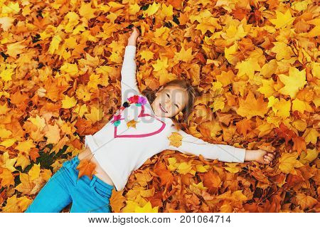 Autumn portrait of a cute little girl of 8 years old playing with yellow leaves in the park top view