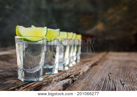 Vodka and lime slices on wooden background.