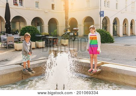 Kids playing by the fountain on summer day. Image taken in Aigues-Mortes Camargue in Languedoc-Roussillon France