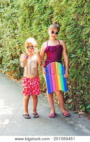 Funny kids on summer vacation wearing swim suits and sunglasses