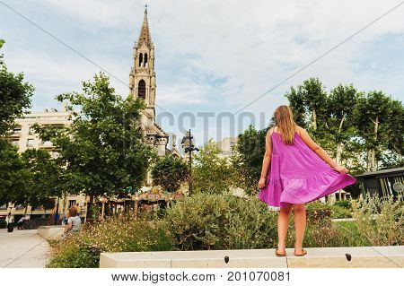 Little kid girl enjoying summer vacation on south of France child admiring St. Perpetua Church Nimes. Back view