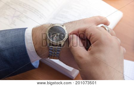 A man in a shirt and jacket adjusts the watch. Nearby lies the book and notepad