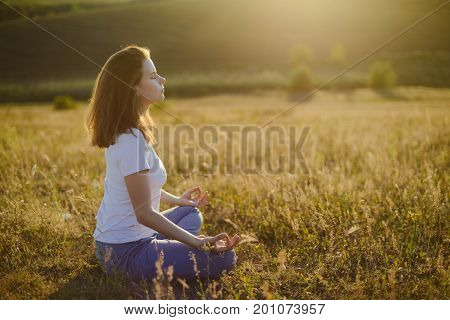 Woman Practices Yoga And Meditates In The Lotus Position On The Nature.  Girl Meditate At The Mounta