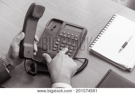 The businessman dials the number on the landline phone holds the handset in the hand. Nearby is a notebook and pen. In frame only hands hand watches. Black and white photo