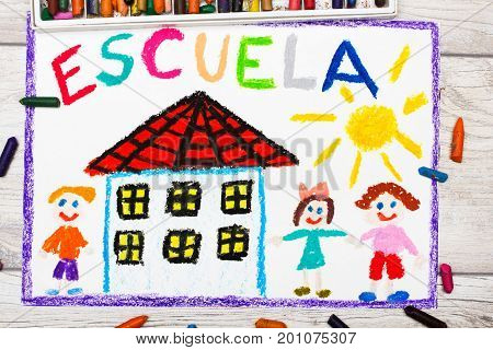 Photo of colorful drawing: Spanish word SCHOOL school building and happy children. First day at school.