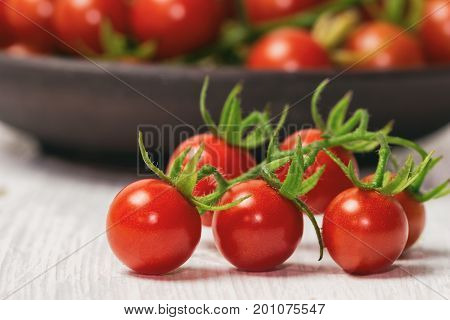 Fresh cherry tomato on white wood table. Close up lovely cherry tomato for background or wallpaper. Prepare fresh cherry tomato for home cooking look so delicious. Side view macro concept. Red cherry tomato concept.