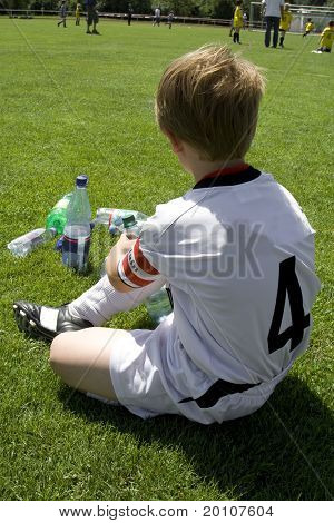exausted boy takes a rest in the halftime of a football match poster