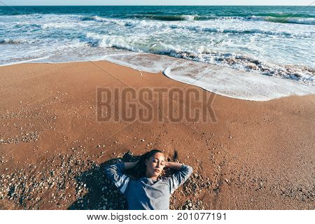 Young girl in sweater relaxing on sand by sea wave. Chilling on the coast and breathing fresh breeze in sunlight. Lazy warm weekend. Fall beach holiday concept. Top view, VSCO instagram filter effect.