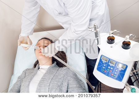 ENT physician looking into patient's ear with an instrument. Doctor young man. The patient is a young woman. treatment of diseases of the ear with special equipment and a solution under pressure