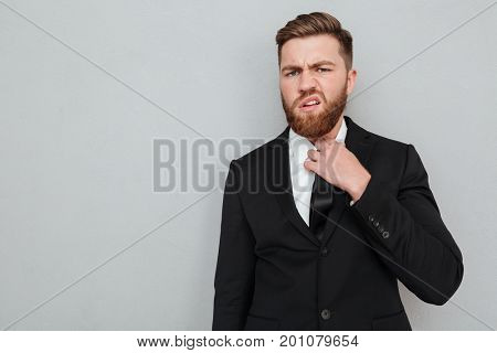 Displeased bearded man in suit over gray background which looking at the camera