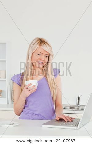 Attractive Blonde Female Holding A Cup Of Coffee And Relaxing On A Laptop In The Kitchen