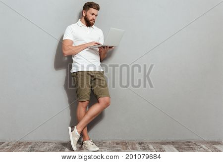 Full length image of bearded man using laptop computer in studio over gray background