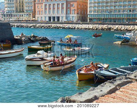 Naples Italy - August 7 2017. People enjoying the a sunbathing in fishing boats moored in Borgo Marinari harbor of Megaride island. Naples. Campania Italy.