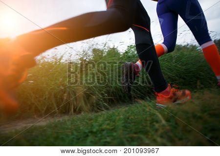 Photo from below of two running sportswomen in park