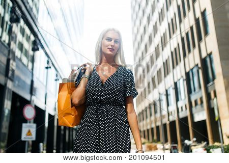 Photo of woman in dress with purchases on city street near buildings
