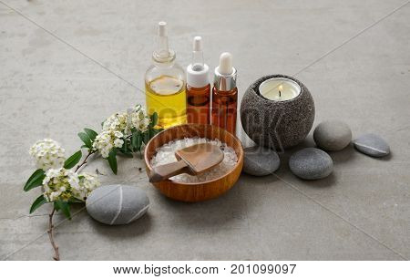 spa setting with tropical flowers,ball,candle ,salt in bowl,stones ,oil on gray background