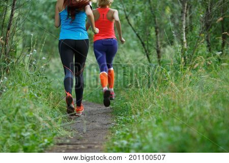 Two athletic women in morning forest