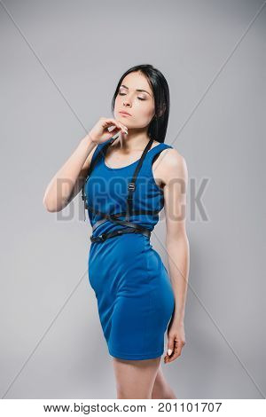 lifestyle, fashion and people concept: pretty woman wearing dark blue dress and swordbelt, posing on white background