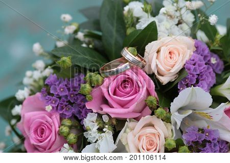 infinity sign of the rings wedding rings on a wood wedding bands wedding rings lie near bouquet of white and pink peach roses a bouquet of roses wedding flowers