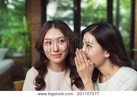 Portrait of a girl telling secrets to her amazed friend in the living room at home