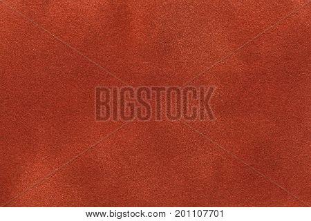 Background of dark orange suede fabric closeup. Velvet matt texture of ginger nubuck textile.