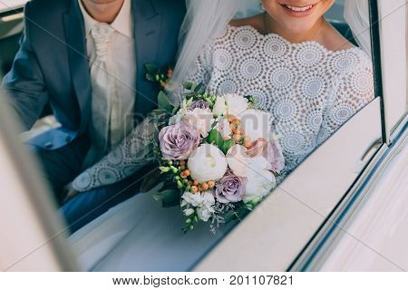 Beautiful bride in a white dress and groom in tuxedo are sitting in a car and holding a wedding bouquet. Groom embrace woman by the waist. Outdoors. Artwork