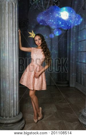 Pretty romantic lady with drawing dream.Beautiful young woman in a pink lacy dress in a vintage luxury grey interior. long curly hair fashion makeup